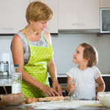 Happy child with woman making meat dumplings Stock Photo