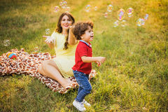 Happy child and woman playing with soap bubble royalty free stock photos