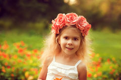 Happy child in wreath of flowers outdoors in summer park Royalty Free Stock Photos