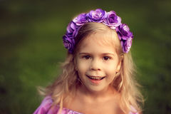 Happy child in wreath of flowers outdoors in summer park Royalty Free Stock Photo