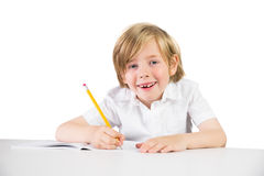 Happy child writing down homework Stock Images
