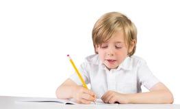 Happy child writing down homework Stock Photo