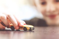 Happy child 6-8 years play with his car toy. Happy child 6-8 years playing with cars and toys at home, indoor stock photography