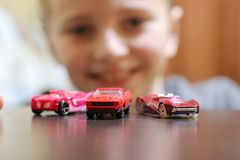 Happy child 6-8 years play with his car toy. Happy child 6-8 years playing with cars and toys at home, indoor stock image