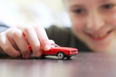 Happy child 6-8 years play with his car toy. Happy child 6-8 years playing with cars and toys at home, indoor stock photos