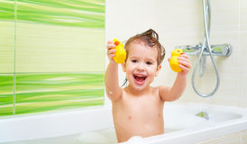 Happy child with yellow duck toys bathes in  bath with foam and Royalty Free Stock Photos