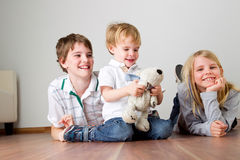 Happy childhood. Playing and laughing children lying on the floor stock photo