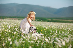 Happy childhood. Happy baby girl stroking her dog in camomile field Royalty Free Stock Photography