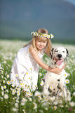 Happy childhood. Happy baby girl hugging her dog in camomile field Stock Images