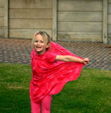 Happy childhood. A happy child in a pink dress playing in the garden with a smiling expression on her face Stock Images