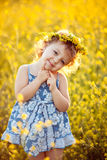 Happy childhood. Baby girl in wreath in field Royalty Free Stock Photos