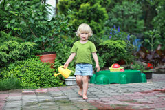 Happy childhood - barefoot girl with watering can Stock Photo