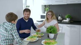 Happy childhood, bearded husband and wife with beverage in hands call son on breakfast. In kitchen stock video footage