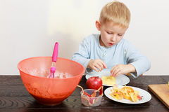 Happy childhood. Boy child kid making drop scones. At home. stock photography