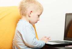 Happy childhood. Boy child kid playing on laptop. At home. Royalty Free Stock Image