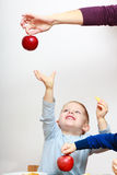 Happy childhood. Boy child kid reaching for apple fruit. At home. Royalty Free Stock Photography