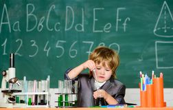 Happy childhood. Boy near microscope and test tubes school classroom. Knowledge concept. Knowledge day. Kid study stock photo
