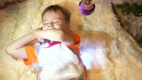 The child plays in the children`s room with a Christmas light, a garland. The boy lies on a white fluffy blanket. Happy. Happy childhood. The child plays in the stock video