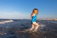 Happy childhood. Happy child in the sea. Rimini resort. Italy. Little blonde girl running in the sea. Vacation stock photos