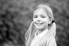 Happy childhood and childcare. Child with smile on cute face outdoor. Little girl with long blond hair. Beauty kid with. Fresh look and skin. Beauty look and royalty free stock images