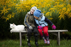Happy childhood. Children with a white cat sit on a bench Royalty Free Stock Image