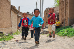 Happy childhood. China Children `s Day, In an ancient village, three children innocently ran, vivid, lively Stock Images