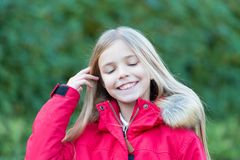 Happy childhood concept. Child with closed eyes enjoy idyllic autumn day. Innocence, purity and youth. Beauty, nature, growth. Girl with blond long hair smile Royalty Free Stock Photos