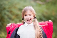 Happy childhood concept. Girl with blond hair ponytail smile on natural landscape. Beauty, look, hairstyle. Kid fashion and style. Child in red coat on idyllic Royalty Free Stock Photo