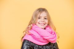 Happy childhood concept. Girl in pink scarf on orange background. Kid beauty, look, hairstyle. Autumn fashion, style, trend. Child model smile with long blond Royalty Free Stock Images