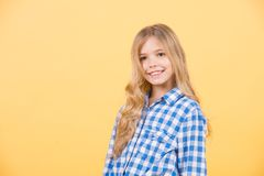 Happy childhood concept. Child model smile with long blond hair. Beauty, look, hairstyle. Kid fashion, style, trend. Girl in blue plaid shirt on orange Stock Photo