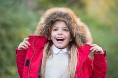 Happy childhood concept. Girl smile on natural landscape. Leisure, activity, lifestyle. Child in red coat and hood with fur outdoor. Kid enjoy autumn nature Royalty Free Stock Image