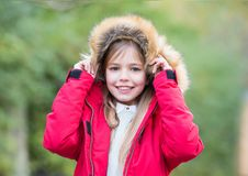 Happy childhood concept. Kid enjoy autumn nature. Child in red coat and hood with fur outdoor. Leisure, activity, lifestyle. Girl smile on natural landscape Stock Photography