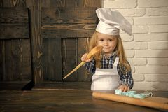 Happy childhood concept. Homemade cooking and baking. Boy cook in chef hat and apron in kitchen. Playing and learning. Child using spoon, rolling pin and stock images