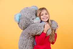 Happy childhood concept. Kid with animal doll, present and gift. Child smile with grey soft toy. Girl hug big teddy bear on orange background. Holiday stock images
