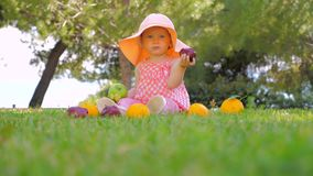 Happy childhood concept. Leisure activities for baby. Girl playing with fruits outdoor. Child in panama having fun. Beautiful girl holding green and red apples stock video