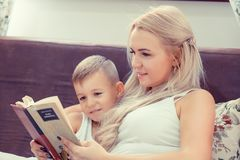 Happy childhood concept. Mom and son reading a book in the bed r royalty free stock photos