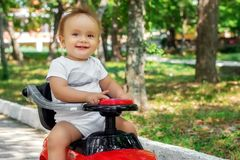 Happy childhood concept: portrait of a cheerful little toddler child sitting leaned back on a red push car and smiling stock image