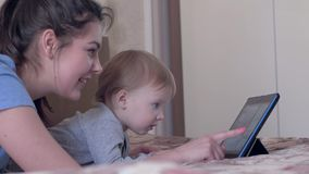 Happy childhood, cute kid boy with smiling mother watch cartoons on touch tablet lying on bed at home. Closeup stock video