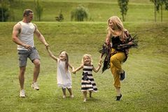 Happy childhood, family, love. Children and parents jump on green grass. Mothers and fathers day. Girls, women and men smile on summer landscape. Freedom Royalty Free Stock Photo