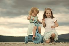 Happy childhood, family, love. Children playing in mountain. Travelling, adventure, wanderlust. Summer vacation concept. Girl ride tricycle with sister on Stock Images