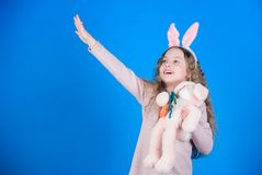 Happy childhood. Get in easter spirit. Bunny ears accessory. Lovely playful bunny child with long hair. Cute and. Adorable. Bunny girl with cute toy on blue stock photos