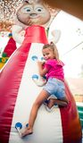 Happy childhood. Smiling little girl climbing and having fun on playground. Space for copy. Looking at camera stock images