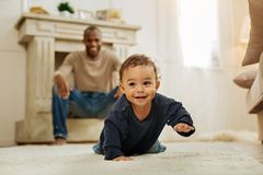 Smiling father watching his son crawling. Happy childhood. Happy dark-haired afro-american men laughing and watching his cheerful young son crawling on the floor royalty free stock image