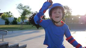 Happy childhood, joyful kid in helmet actively spends leisure at Skate Park on open air in sunlight