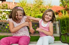 Happy childhood - larking children. Two small girls (sisters) larking in backyard sitting on bench Royalty Free Stock Image