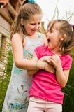 Happy childhood - larking children. Two small children (sisters) having fun in backyard Royalty Free Stock Photos