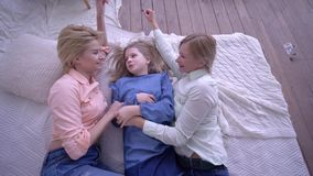 Happy childhood, laughing mum with children girls lie on bed and communicate with each other. At home stock video