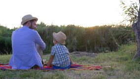 Happy childhood, little boy with father in straw hats enjoy the sunset sitting on a blanket in open air. Happy childhood, little boy with father in straw hats stock video footage