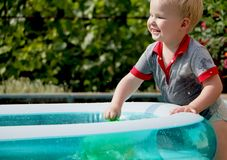 A little boy is playing with water near an inflatable pool. Summer and family holidays. Happy childhood royalty free stock image