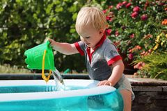 A little boy is playing with water near an inflatable pool. Summer and family holidays. Happy childhood. Happy childhood. A little boy is playing with water near royalty free stock photos
